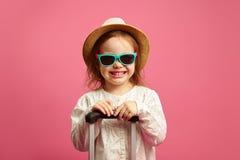 L?chelndes kleines M?dchen in der Sonnenbrille und in Strohhut, Koffer auf lokalisiertem Rosa halten, dr?ckt herzlichst Freude au stockfotografie