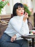 L?cker gourmet- kaka Attraktiv brunett f?r kvinna att ?ta gourmet- bakgrund f?r kakakaf?terrass Gastronomical njutning royaltyfri foto