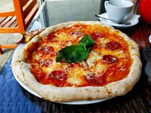 l?cker italiensk pizza Smaklig traditionell italiensk peperonipizza p? den vita plattan royaltyfria foton