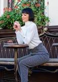 L?cker och gourmet- drink Flickan kopplar av kaf?t med kaffe och efterr?tten Gourmet- begrepp Attraktiv elegant brunett f?r kvinn fotografering för bildbyråer