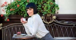 L?cker och gourmet- drink Flickan kopplar av kaf?t med kaffe och efterr?tten Tycker om den attraktiva eleganta brunetten för kvin arkivbilder