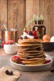 L?ckra, endast lagade mat s?ta pannkakor med djupfrysta b?r p? en vit platta Amerikansk traditionell matr?tt royaltyfri fotografi