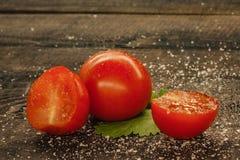 l?ckra k?rsb?rsr?da tomater som strilas med f?r att salta p? en tr?bakgrund royaltyfri foto