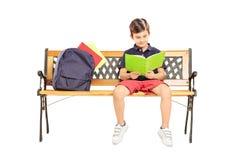 L'écolier a assis sur un banc en bois lisant un livre Photos stock