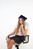 L'écolière avec le diplômé de chapeau s'asseyent sur la chaise, pensant à l'avenir Photographie stock