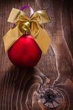 L'or a coloré l'arc de Noël et la babiole rouge sur le vieux conseil en bois Photographie stock libre de droits