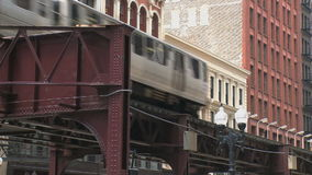 The L cruises through downtown Chicago (2 of 2). Chicago's elevated train system.  Similar to other cities subway system stock video