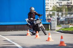 L-driver person driving slalom through the orange cones on motordrome on motorcycle Stock Photo