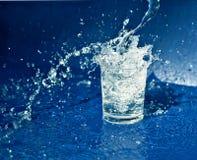 Éclaboussement de l'eau du verre Photo stock