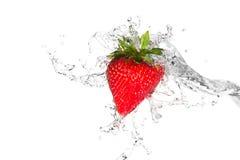 L'eau éclaboussant sur une fraise photographie stock libre de droits