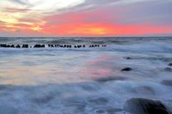 L'eau au-dessus du coucher du soleil côtier de roches Image libre de droits