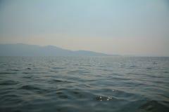 L'eau au loin avec la montagne Photographie stock