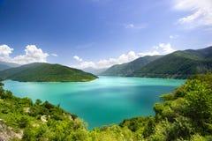 L'eau azurée dans une lagune bleue parmi le fond blanc vert de nuages de ciel bleu de montagnes photographie stock libre de droits