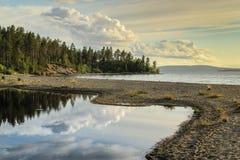 L'eau calme et lisse du lac dans lequel la forêt et les nuages sont reflétés photo stock