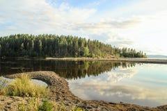 L'eau calme et lisse du lac dans lequel la forêt et les nuages sont reflétés photos libres de droits