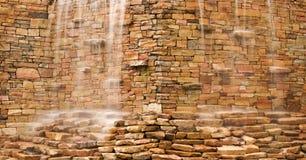 L'eau cascadant au-dessus du mur en pierre Photographie stock libre de droits