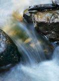 L'eau circulant et se précipitant entre les roches Images stock