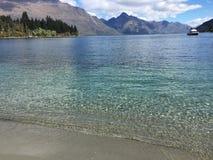 L'eau clair comme de l'eau de roche de turquoise de bord de mer de Queenstown le jour ensoleillé photographie stock