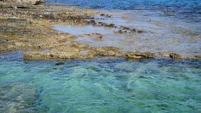 L'eau claire de méditerranéen avec la pierre et le fond arénacé banque de vidéos