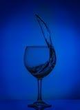 L'eau claire tentant l'éclaboussement abstrait sur le fond de gradient de la couleur bleue sur la surface réfléchie 03 image libre de droits