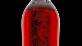 L'eau colorée dans des bouteilles en verre avec la baisse de l'eau et des bulles sur le fond foncé photographie stock