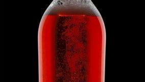 L'eau colorée dans des bouteilles en verre avec la baisse de l'eau et des bulles sur le fond foncé images stock