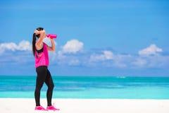 L'eau convenable de boissons de jeune femme sur la plage blanche Photos libres de droits