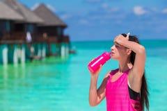 L'eau convenable de boissons de jeune femme sur la plage blanche Image stock