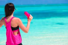 L'eau convenable de boissons de jeune femme sur la plage blanche Photos stock