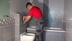 L'eau d'aspiration d'homme de plombier du tuyau du mécanisme de rinçage de toilette banque de vidéos