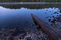 L'eau d'identifiez-vous et sur une plage des pierres photographie stock libre de droits