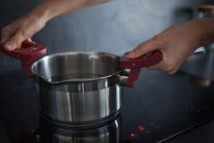 L'eau dans la casserole est sur la fraise-m?re d'induction Cuisson ? la maison photos libres de droits