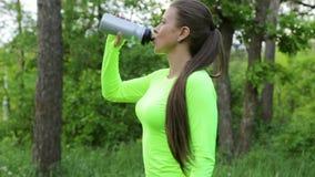 L'eau de boissons de femme après regard de forêt de sport à l'appareil-photo et aux tumbs de sourire d'exposition  banque de vidéos