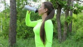 L'eau de boissons de femme après sport dans la forêt regardent alors l'appareil-photo et le sourire banque de vidéos