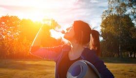L'eau de boissons de fille pendant la séance d'entraînement Photos libres de droits