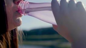 L'eau de boissons de femme Portrait dans la jeune femme assoiffée de profil avec de l'eau potable de longs cheveux Fermez-vous ve clips vidéos