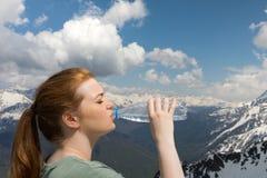 L'eau de boissons de jeune femme de la bouteille en plastique dans les montagnes sur la neige fait une pointe le fond photos libres de droits