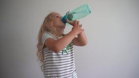 L'eau de boissons de petite fille du flacon bleu de bouteille sur le fond blanc cardan banque de vidéos