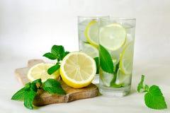 L'eau de detox de menthe de citron Limonade faite maison avec la menthe, le citron et la glace en verres Conseil en bois, citron  Photos stock