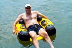 l'eau de flottement de tube d'homme Photo stock