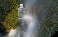 L'eau de Flwoing avec la bouteille Images stock