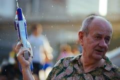 L'eau de jeu de vieil homme pendant le Songkran Photos stock