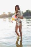 L'eau de marche de cuvette de fille avec le chien dans sa main Image stock