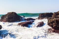 L'eau de mer bleue blanche ondule des roches de marée haute Images stock