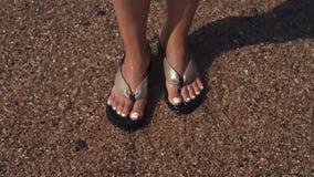 L'eau de mer claire lave les pieds femelles chaussés dans des bascules électroniques, plan rapproché banque de vidéos