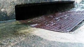 L'eau de pluie fonctionnant dans un drain de tempête banque de vidéos