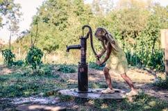 L'eau de pompage de petit enfant du puits d'eau photo stock