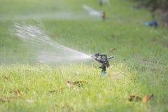 L'eau de pulvérisation d'arroseuse de l'eau de pelouse au-dessus de l'herbe Photographie stock libre de droits