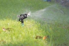 L'eau de pulvérisation d'arroseuse de l'eau de pelouse au-dessus de l'herbe Images libres de droits