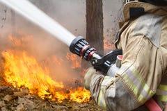 L'eau de pulvérisation de sapeurs-pompiers au feu de brousse photos libres de droits